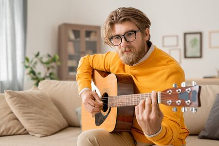 Young contemporary male musician in casualwear playing acoustic guitar Stok Fotoğraf