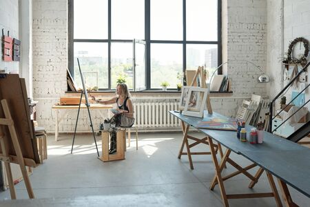 Female artist sitting in front on canvas and painting picture in own spacious studio
