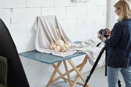 Rear view of mature lady in denim jacket photographing vegetable against fabric in photo studio