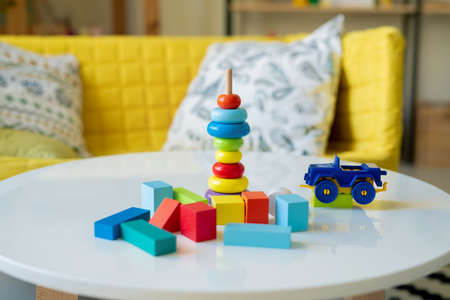 Large group of small wooden cubes of various colors, plastic lorry and stack of blue, yellow and red sections of toy on stick on table 免版税图像