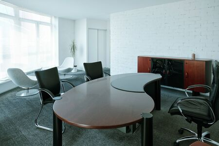 Interior of large contemporary boardroom with chairs around design table, two white armchairs near by and wooden cabinet along brick wall
