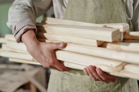 Close-up of unrecognizable carpenter in apron carrying heap of wooden planks to make furniture
