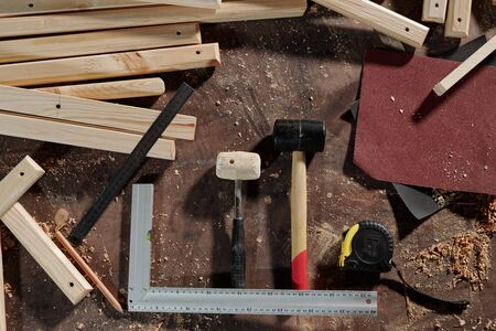 Above view of carpenters tools such as hammers, tape measure, sandpapers, rulers and pencil places on desk with wooden planks and shavings Stok Fotoğraf