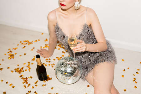 Pretty relaxed girl in glamorous dress holding flute of champagne while sitting on the floor with golden confetti, bottle and discoball