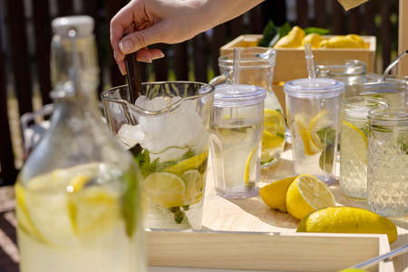 Hand of young female squeezing lemon slices in water and mixing them with ice cubes in glass jug by table while making fresh lemonade