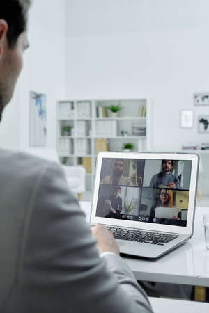 Over shoulder view of businessman sitting at desk in office and talking to colleagues via video conferencing on laptop