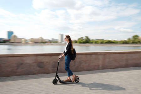 Young carefree female in casualwear and sunglasses moving on electric scooter