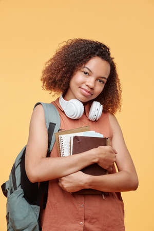Portrait of content beautiful Afro-American high school student with wireless headphones around neck embracing workbooks against yellow background Banque d'images