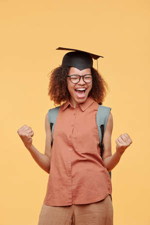 Ecstatic African-American student girl in graduation cap making yes gesture after successfully passed exams
