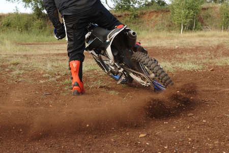 Rear view of unrecognizable man in red boots drifting motorbike on off-road track while stop it Standard-Bild