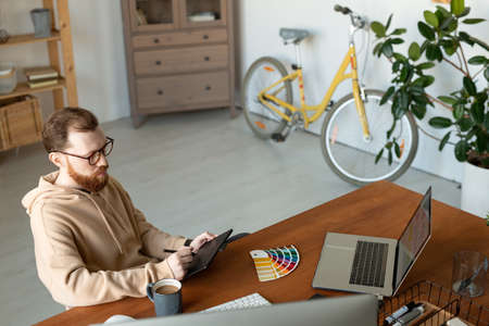 Serious hipster young graphic designer in eyeglasses sitting at table in home office with bicycle and working on digitizer tablet Banco de Imagens