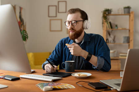 Busy young bearded designer in wireless headphones sitting at table in home office and eating cookies while working with computer and digitizer