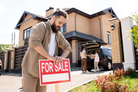 Young bearded father placing For sale sign into ground near house while putting house up for sale