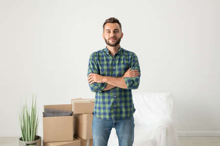 Portrait of content handsome young man in checkered shirt standing with crossed arms in new flat with moving boxes