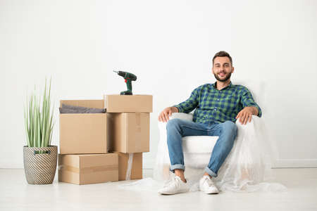 Portrait of smiling relaxed young bearded man sitting in armchair covered with napkin in new house with moving boxes 写真素材