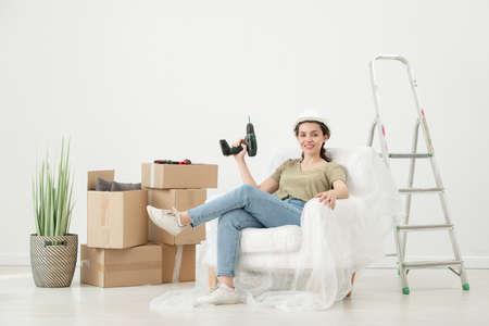 Portrait of smiling young woman in hardhat sitting with cordless screwdriver in armchair under cover in room with moving boxes 写真素材