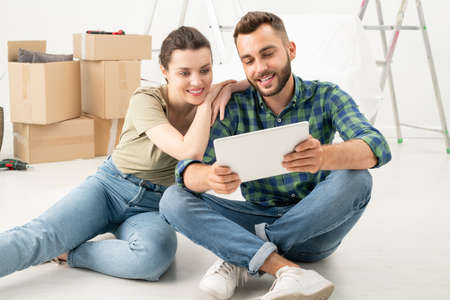 Smiling young couple sitting on floor in new flat and ordering furniture online using tablet 写真素材