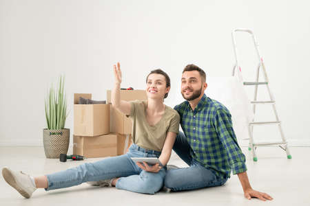 Positive young couple sitting on floor in new apartment with moving stuff and using design app on tablet while discussing interior