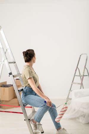Rear view of brunette woman in jeans sitting with paint roller on step of ladder and looking at painted wall