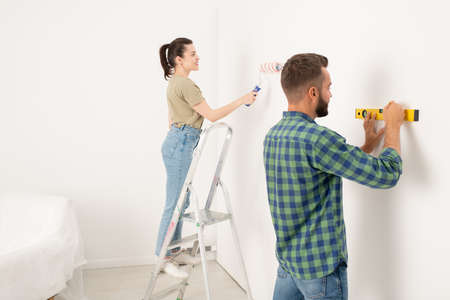 Content young woman standing on stepladder and painting wall while her boyfriend drawing line using level 写真素材