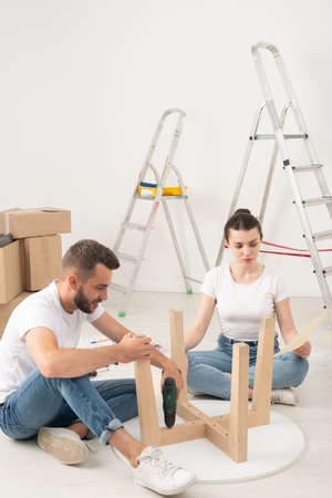 Young couple moving into new house sitting on floor and assembling coffee table together 写真素材