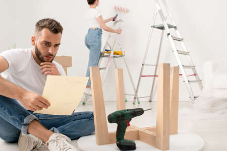 Serious young bearded man sitting with crossed legs on floor and reading instruction while assembling furniture in new apartment 写真素材