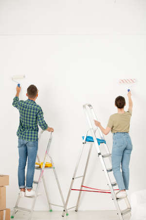 Rear view of young couple in casual clothing standing on stepladders and paining wall with paint roller while making interior of dream in new flat