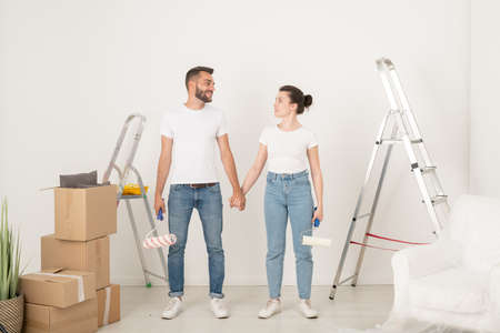 Smiling young couple in jeans holding hands and looking at each other while supporting each other during remodeling room 写真素材