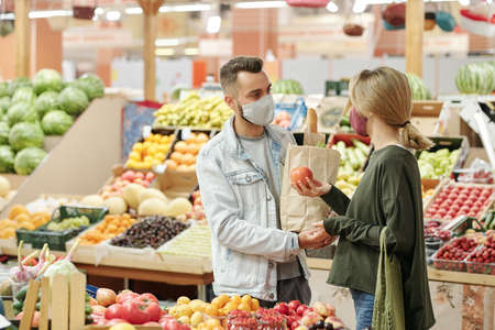 Young couple in cloth masks standing at counter and buying organic food at market: girl choosing tomatoes
