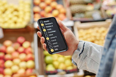 Close-up of unrecognizable man using check-list app while buying food at farmers market