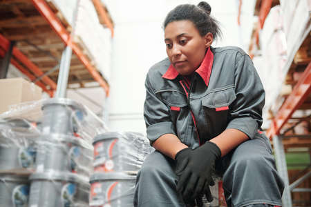Young restful female manager of large warehouse or storage room of hypermarket