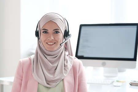 Portrait of positive beautiful young Muslim woman in hijab answering questions using hands-free device in call center