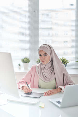 Busy young Muslim graphic designer in beautiful hijab sitting at desk and using digitizer for work