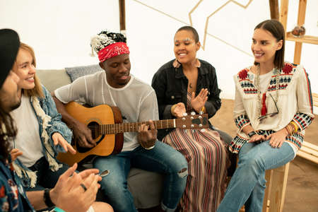 Positive young black musician playing guitar and singing song with friends in tent