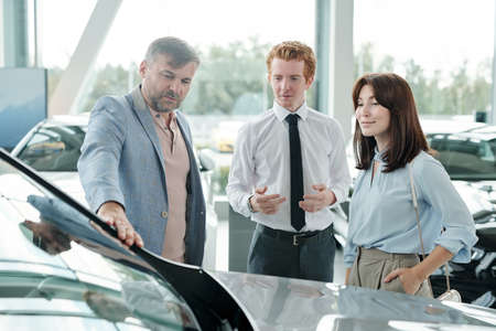 Elegant mature man touching front window of new car in large auto center