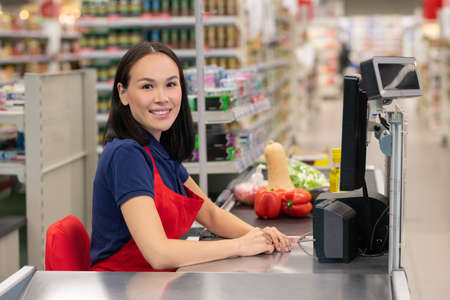 Cheerful woman working in supermarket sitting at cash desk looking at camera smiling