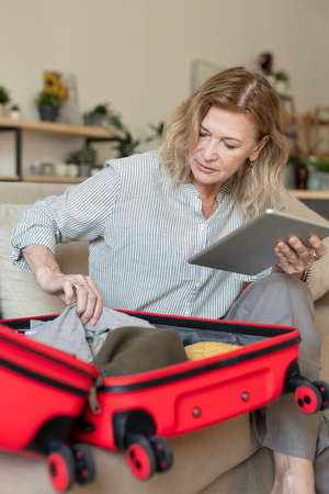 Mature blond woman with touchpad putting clothes and other stuff into suitcase
