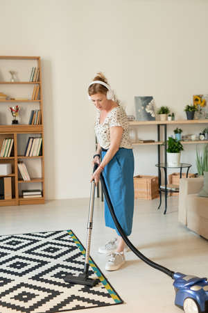 Contemporary mature woman cleaning the floor in living-room with vacuum cleaner