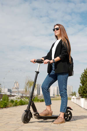 Elegant young businesswoman in casualwear standing on electric scooter on road