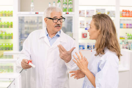 Senior male pharmacist holding new medicaments while consulting his assistant