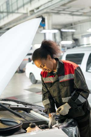 Young worker of car maintenance service standing by open engine compartment