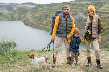 Happy young family of three in warm casualwear and their small dog on trip