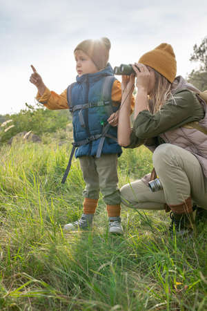 Young woman with binoculars looking where her cute little son pointing
