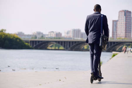 Back view of young elegant businessman in formalwear moving on electric scooter