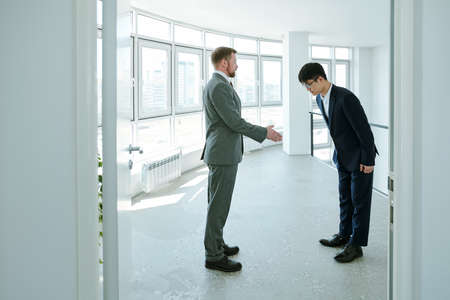 Young successful businessman in formalwear greeting Asian business partner