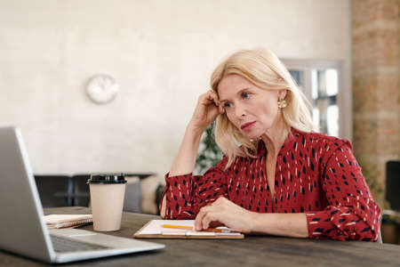 Serious mature blond businesswoman looking at online data on laptop display