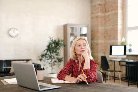Pensive mature blond businesswoman sitting in front of laptop and contemplating 版權商用圖片