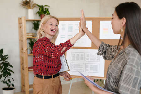 Two successful businesswomen in smart casualwear giving one another high five