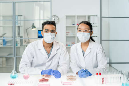 Two young intercultural clinicians in whitecoats, protective masks and gloves