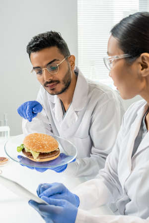 Male worker of food quality control pointing at hamburger with vegetable meat